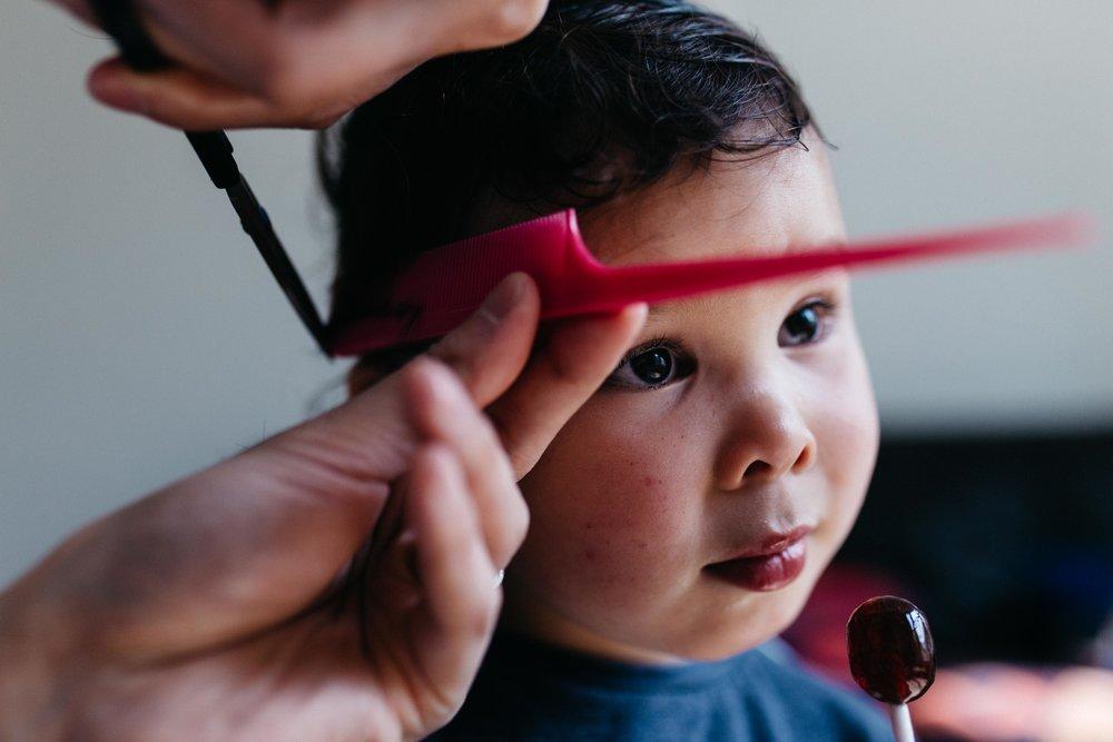 Boy having an haircut  while eating a lollipop