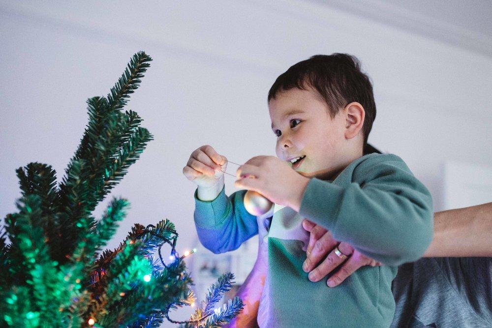 Boy reaching top of Christmas tree