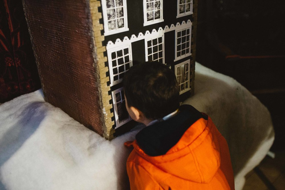 Boy looking through model house