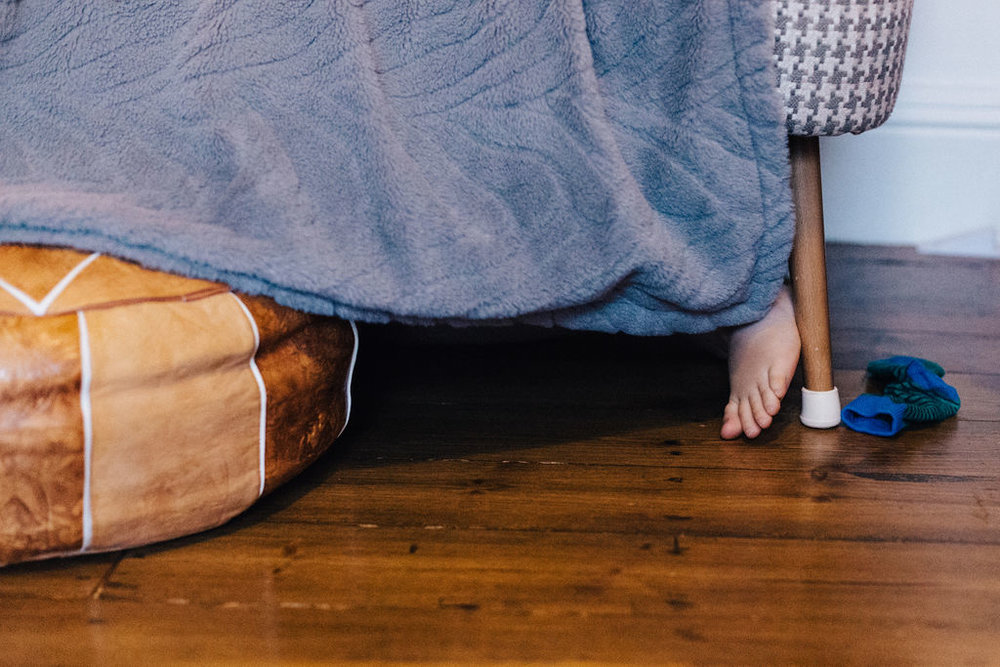 Child's foot under sofa