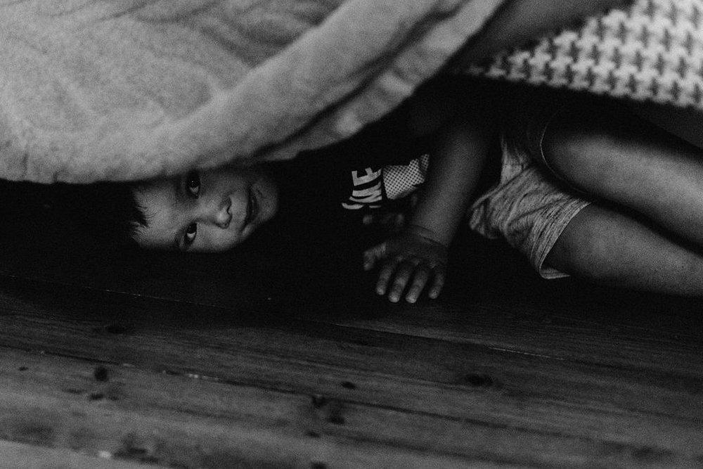 Boy hidding under a sofa
