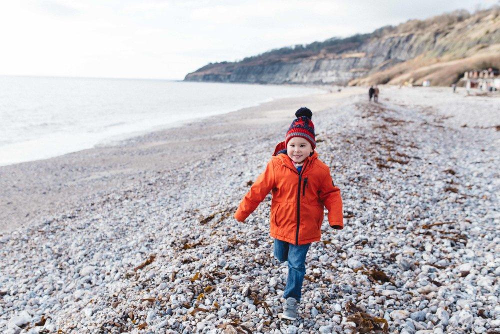 Happy boy running on Lyme Regis beach
