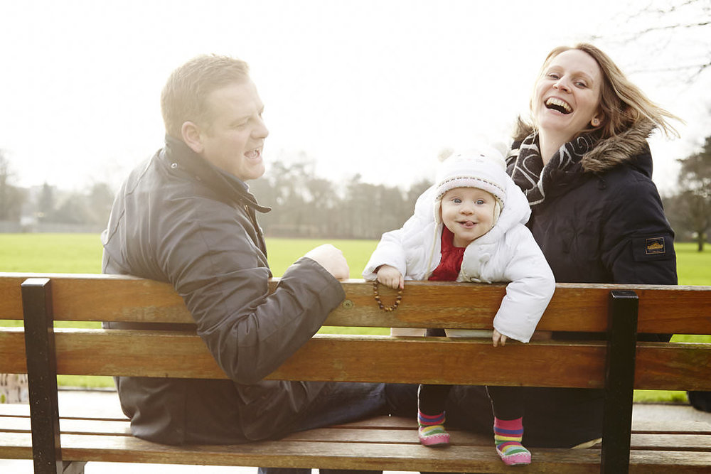 Parents with toddler girl on bench in Cator Park during family photoshoot in Beckenham