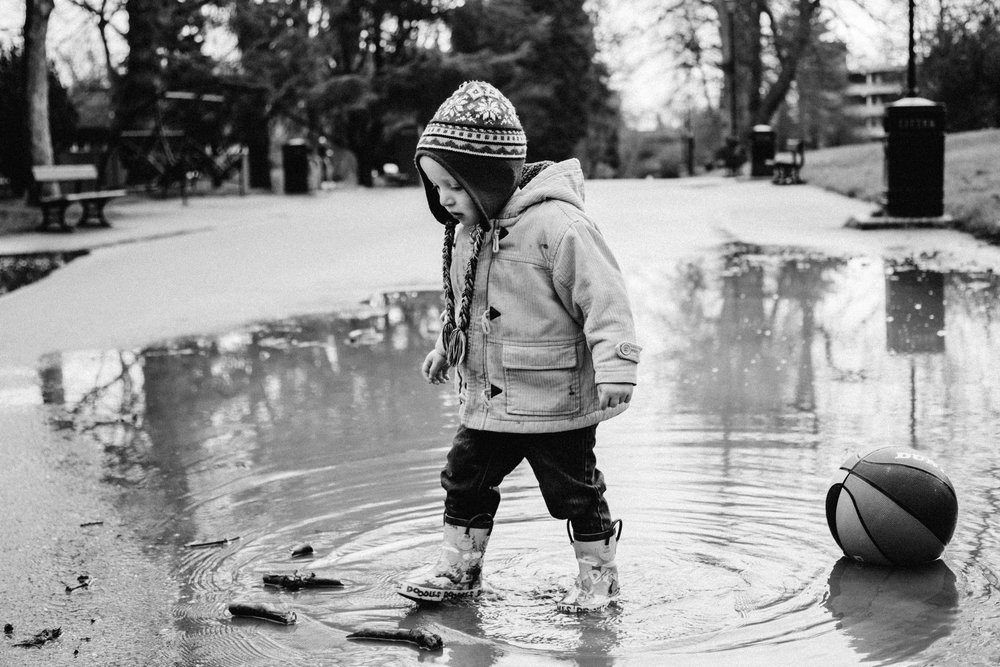 Boy playing in puddle in Crystal Palace Park during family photography session
