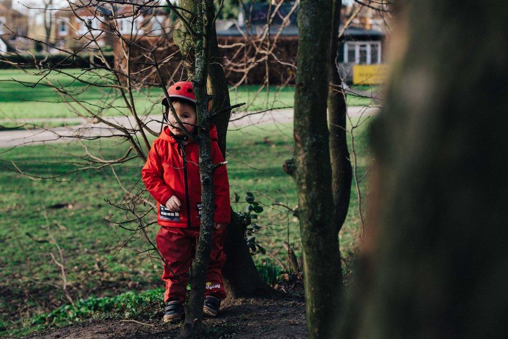 Boy hiding behind tree in Cator Park, Beckenham