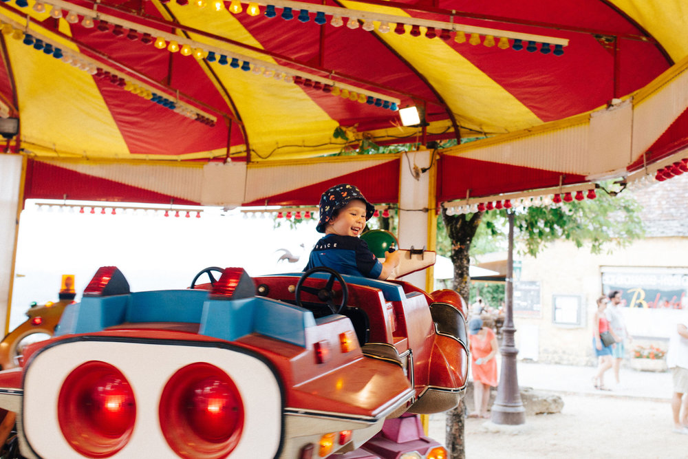 Little boy on carousel in Domme, Dordogne