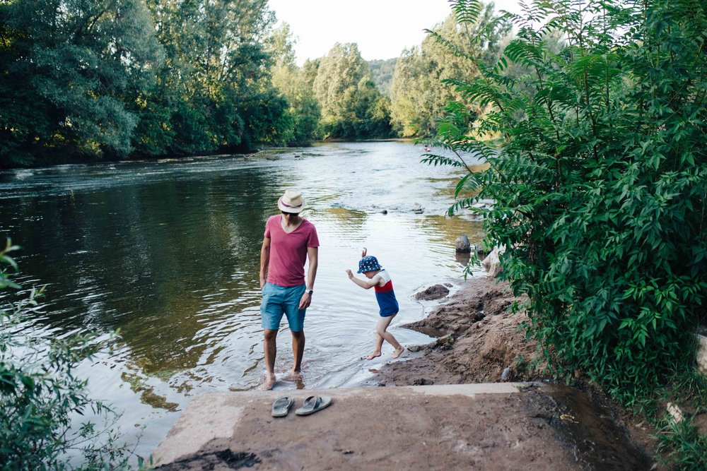 Boy jumping in the river Vezere in France next to father
