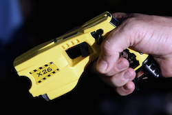 A municipal policeman in Nice poses with the Taser X26 model