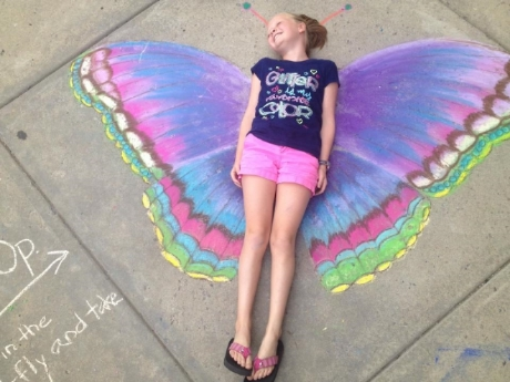 Olivia takes a photo opp in the butterfly wings created by Jen Gray.
