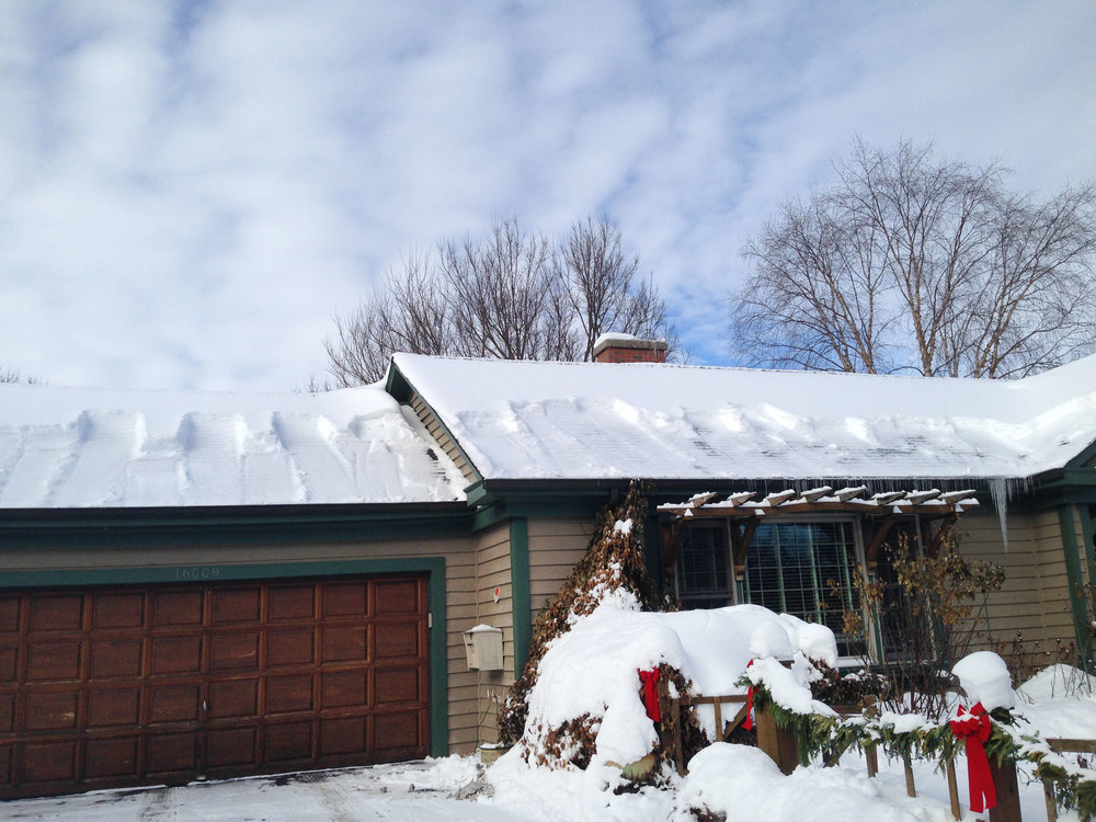 "A recently ""shoveled"" roof, clearing the snow from the overhanging eaves and helping to prevent ice damming and interior water damage."
