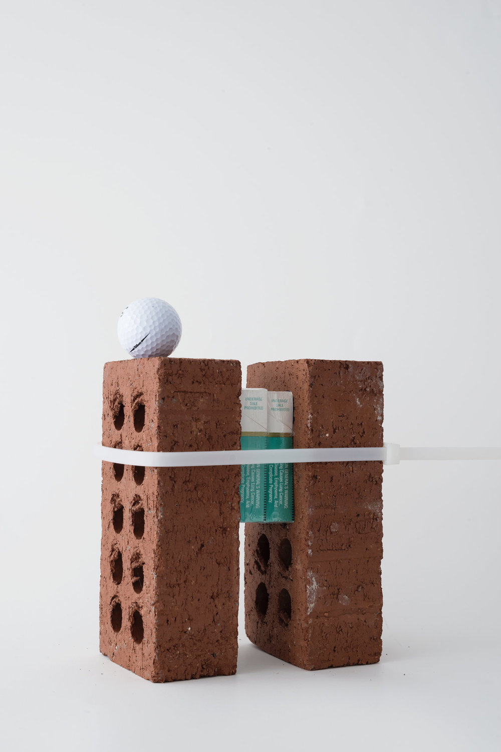""" Lights On Or Off My Lungs""  Golf Ball, Plasic, Bricks, Packs of Cigarettes.  Dimensions Variable  2018  © Messiah Joshua LLC"