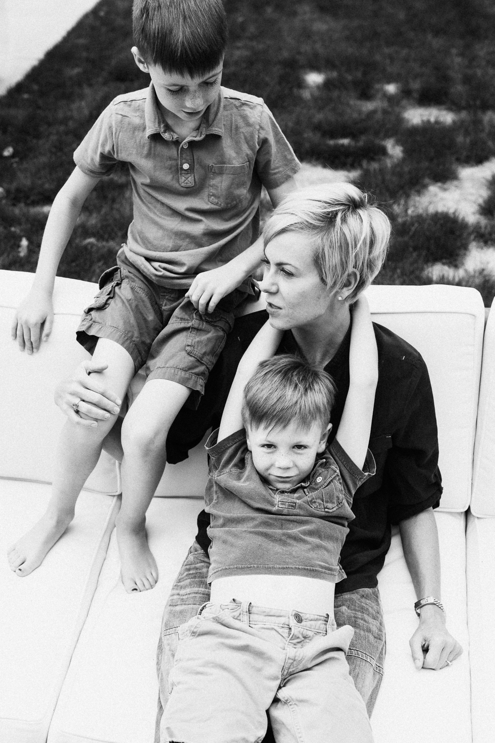 candid-black-and-white-photo-of-mom-and-sons-in-backyard-sugarhouse-utah