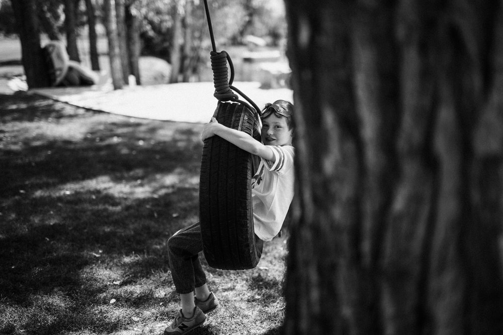black-and-white-portrait-of-boy-on-tire-swing-in-heber-utah
