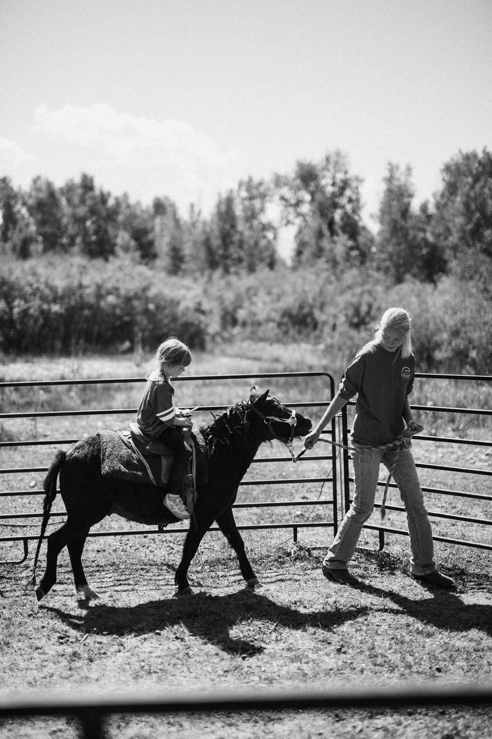 black-and-white-documentary-photograph-of-little-girl-riding-miniature-horse-in-heber-utah