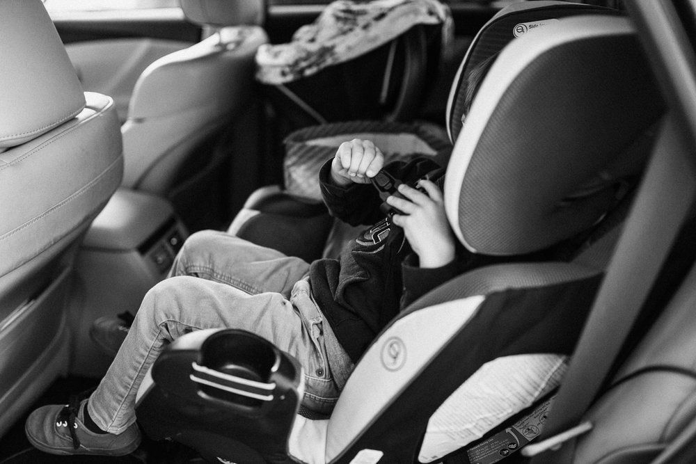 candid day in the life shot of young boy buckling himself in car san diego california