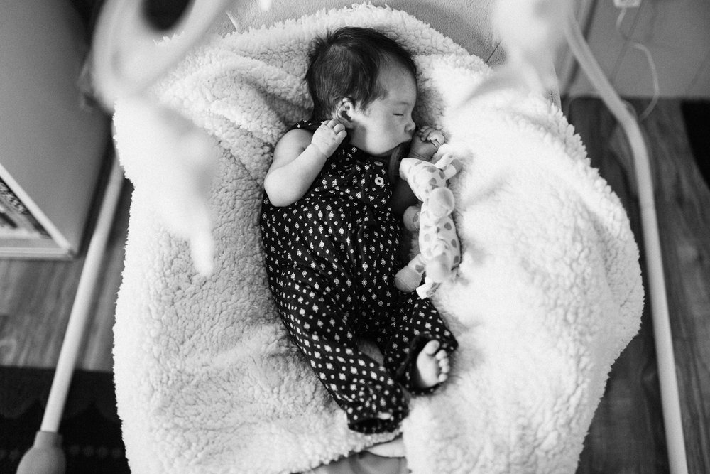 black-and-white-candid-shot-of-sleeping-baby-at-day-in-the-life-session-san-diego-ca