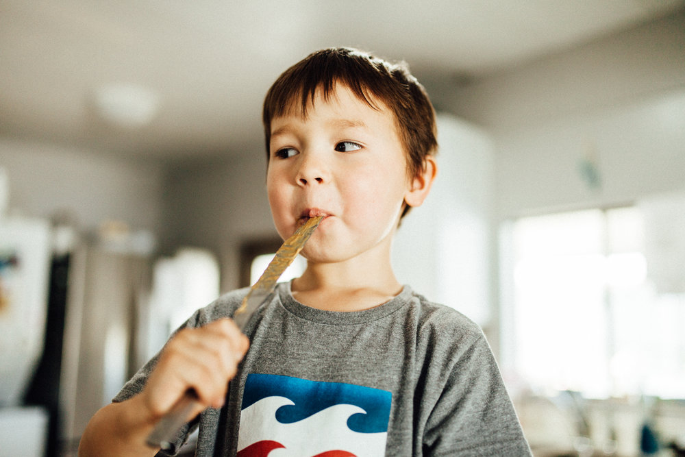 boy-licking-peanut-butter-off-knife-during-in-home-lifestyle-documentary-photo-session-san-diego-california