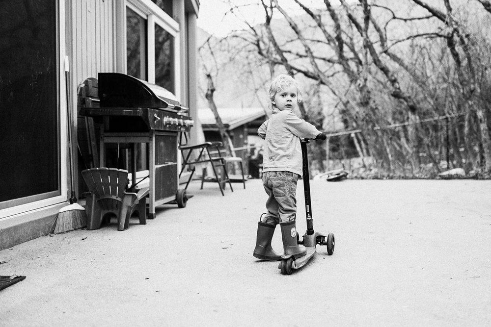 black-and-white-image-of-young-boy-on-scooter-in-home-documentary-photographer