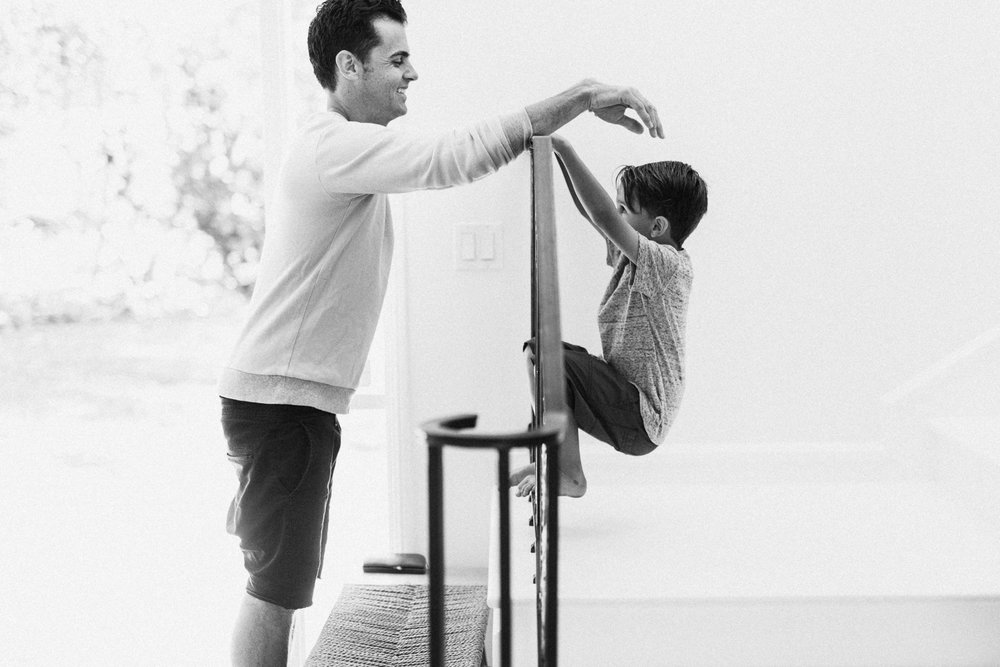 raw-and-authentic-black-and-white-photo-of-dad-kissing-son-in-home-family-shoot-newport-beach-ca