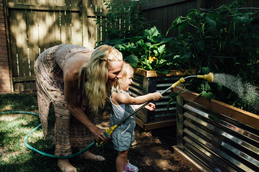 candid-photo-of-mother-and-daughter-watering-garden-during-in-home-photography-session-with-jen-fairchild-slc-ut