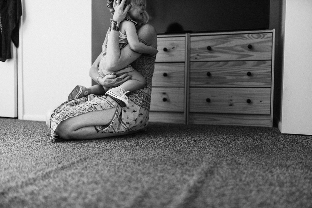 tender-and-intimate-photograph-of-mother-consoling-toddler-during-at-home-lifestyle-photo-session-with-jen-fairchild-sandy-utah