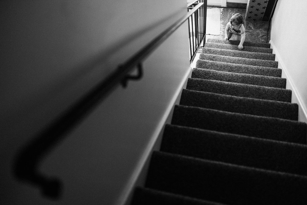 artistic-photo-of-toddler-going-down-stairs-at-home-during-in-home-lifestyle-session-with-jen-fairchild-slc-utah