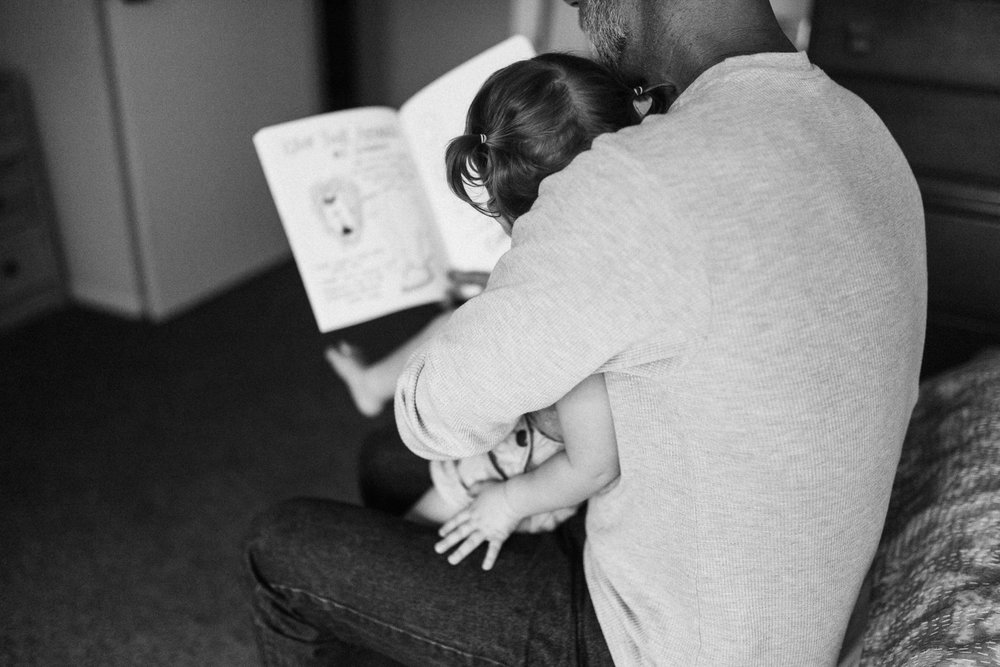 intimate-and-raw-photo-of-dad-reading-to-toddler-during-at-home-photo-session-with-jen-fairchild-slc-utah