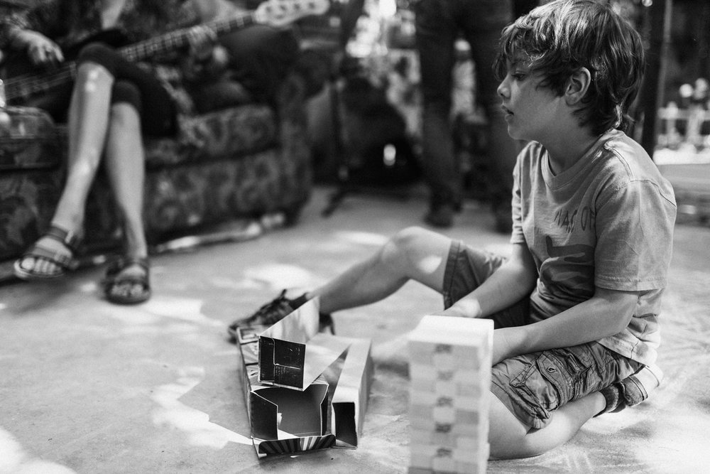 boy-playing-jenga-outside-during-in-home-family-sessions-with-jen-fairchild-photography-in-sugrahouse-slc-ut