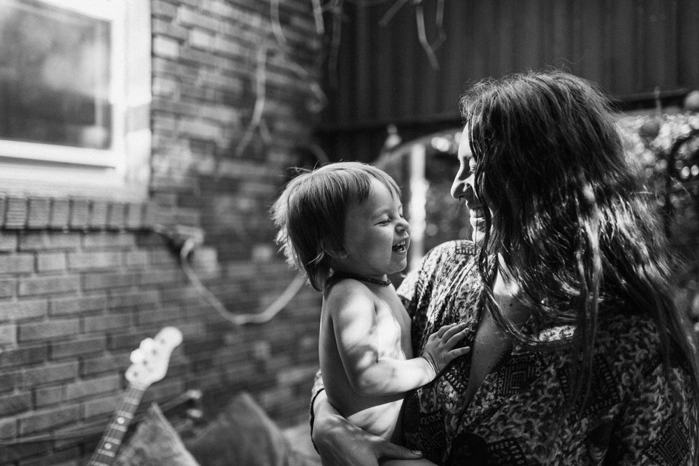 mother-holding-son-in-bakyard-laughing-in-home-family-sessions-for-Nikol0fmaily-with-jen-fairchild-photography-slc-ut