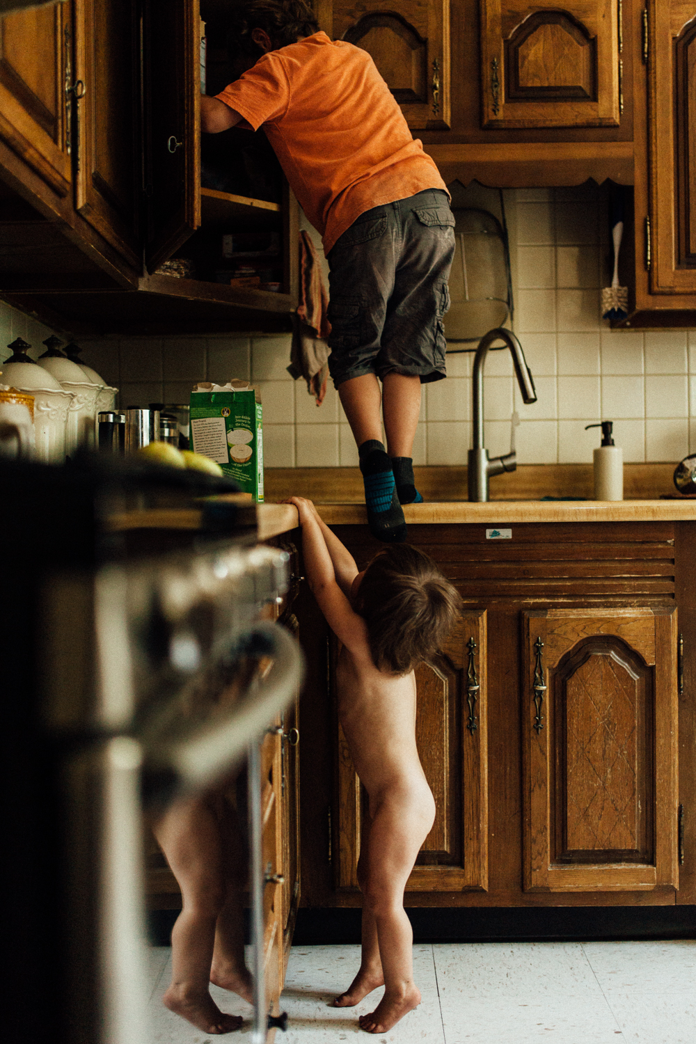 brothers-climbing-on-kitchen-counter-to-sneak-treats-Nikol-family-in-home-photo-session-with-jen-fairchild-photography-sugarhouse-slc-ut