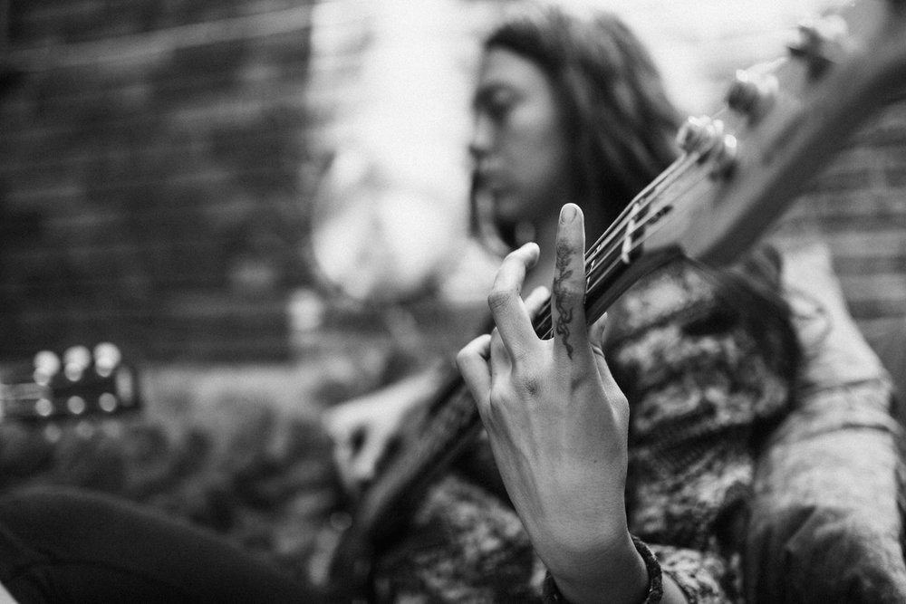 upclose-of-woman-hand-pkaying-chords-on-guitar-in-outdoor-livingroom-family-photos-with-jen-fairchild-photography-salt-lake-utah