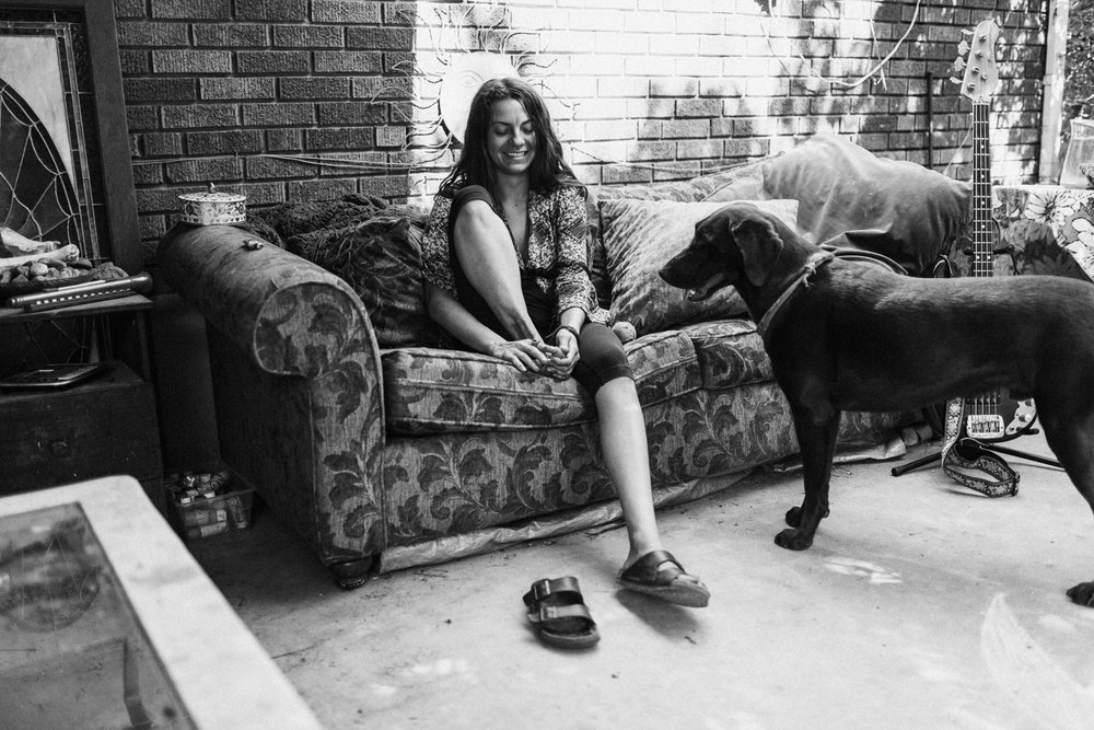 woman-sitting-on-couch-outside-with-black-dog-in-home-photo-session-with-jen-fairchild-photography-sugarhouse-utah