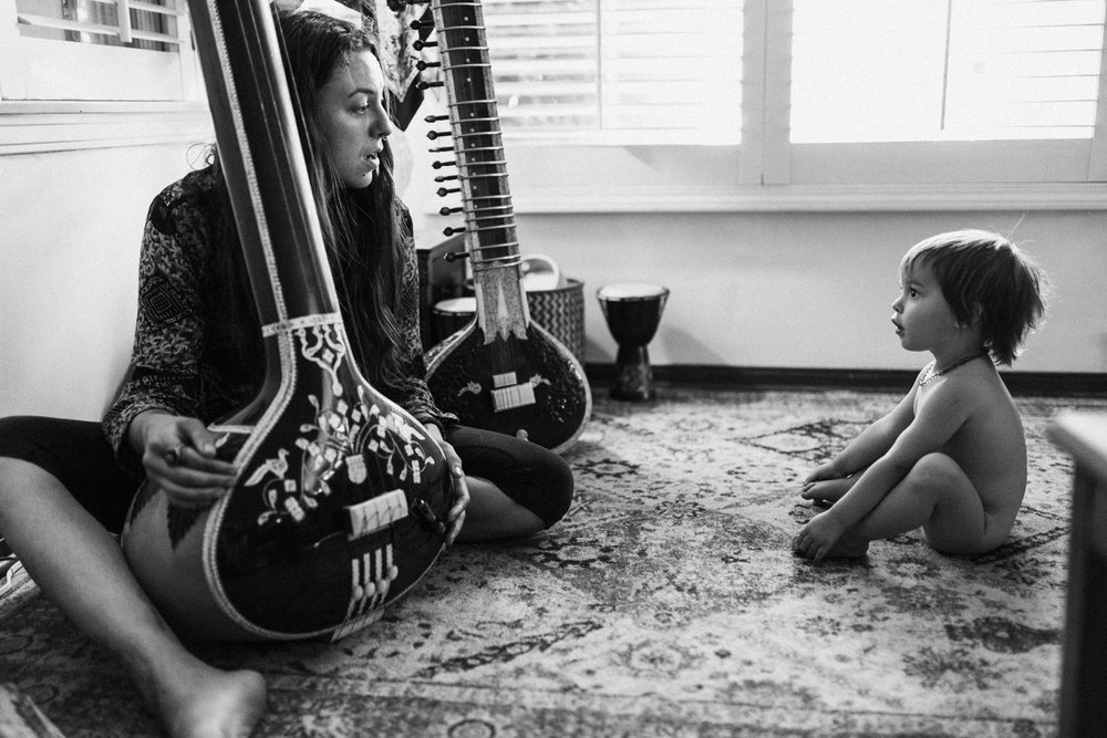 black-and-white-mother-and-daughter-sitting-on-the-ground-playing-instruments-in-home-photo-session-with-jen-fairchild-photography