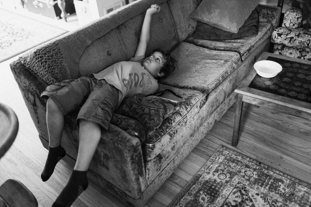 black-and-white-little-boy-stretching-out-on-couch-family-photo-session-with-jen-fairchild-photography-slc-ut