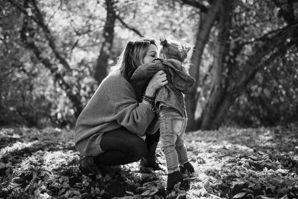 candid-black-and-white-photo-of-mom-kissing-daughter-in-fall-leaves-with-jen-fairchild-photography-in-salt-lake-city-utah
