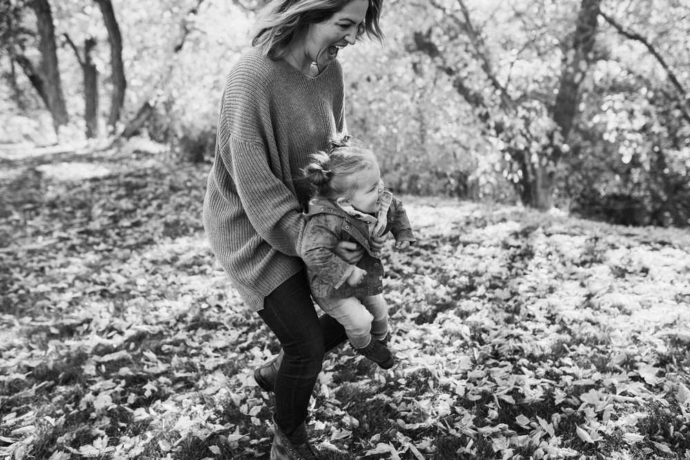 clean-and-natural-mom-carrying-daughter-in-fall-leaves-rotary-glenn-park-during-free-family-portraits-with-jen-fairchild-photography-in-salt-lake-city-utah