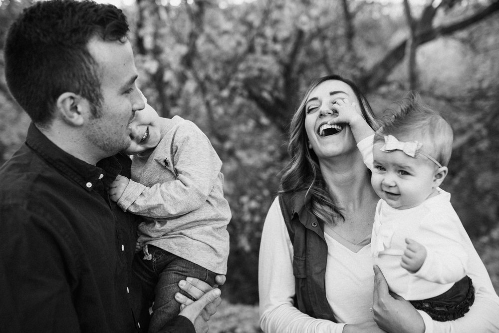 candid-black-and-white-photo-of-family-laughing-during-family-mini-session-with-jen-fairchild-photography-in-salt-lake-city-utah