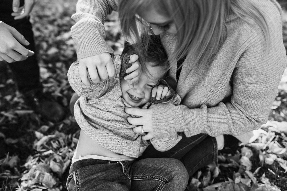 candid-and-intimate-photo-of-mother-tickling-son-in-fall-leaves-with-jen-fairchild-photography-slc-utah