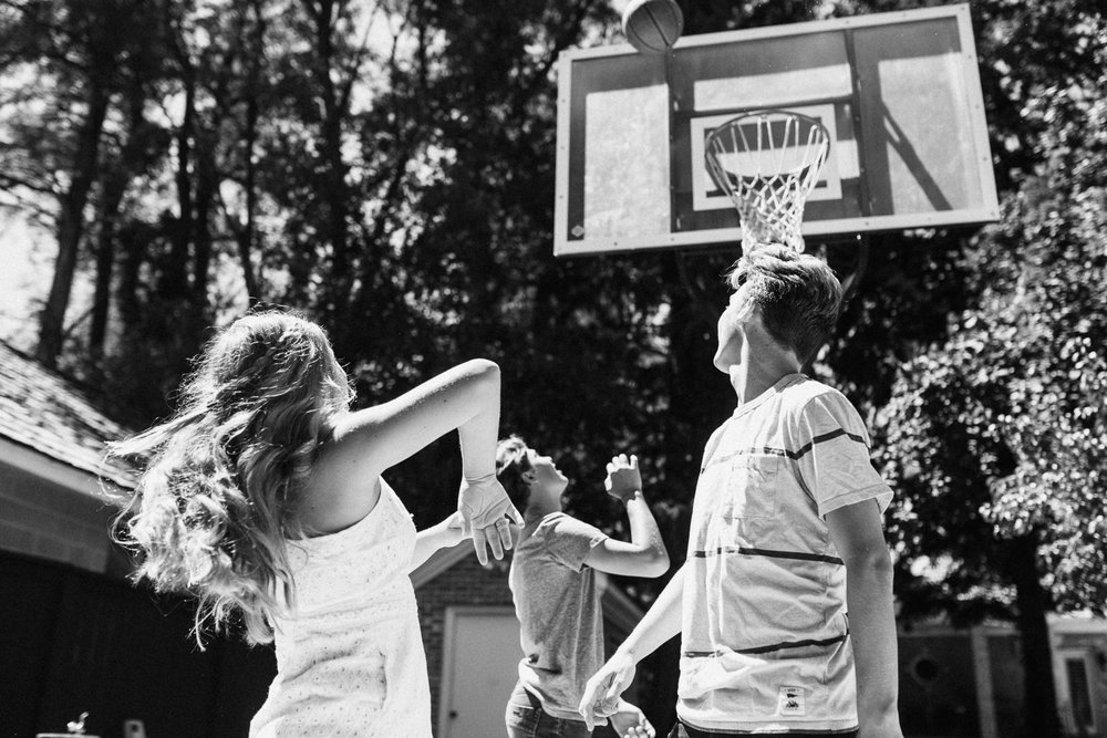 natural-and-artistic-siblings-shooting-hoops-in-backyard-in-salt-lake-city-utah