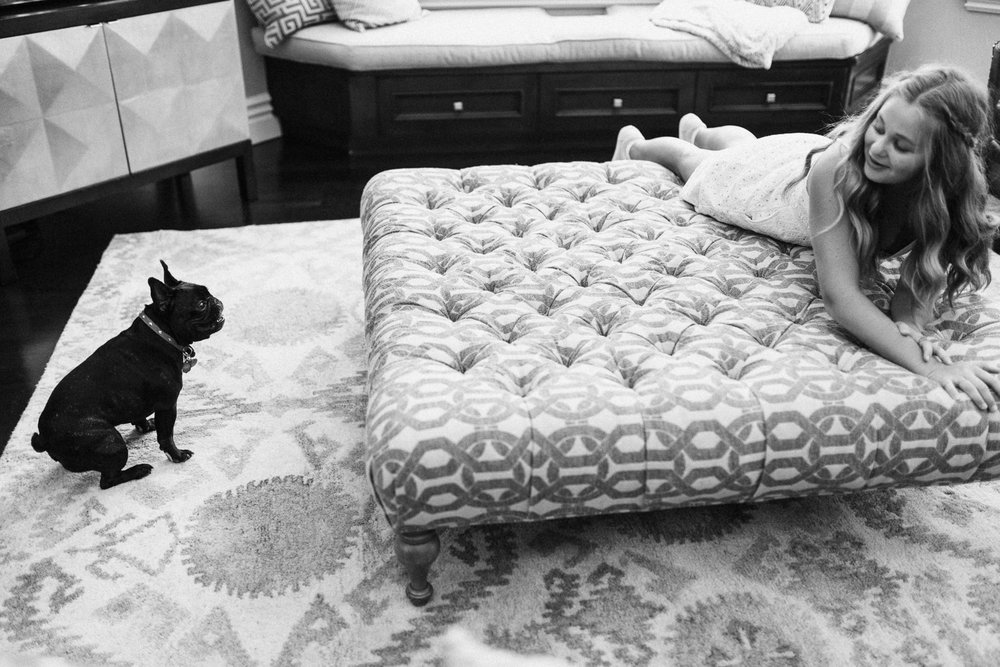 candid-black-and-white-photo-of-girl-sitting-on-ottoman-with-pug-dog-salt-lake-city-utah