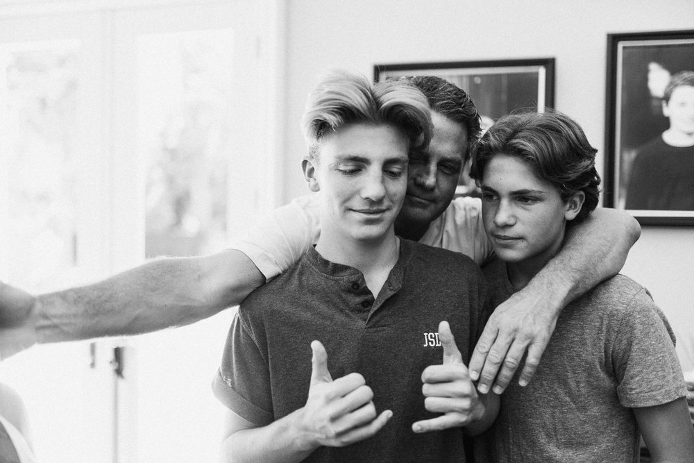 candid-and-natural-black-and-white-photo-of-father-hugging-sons-salt-lake-city-utah