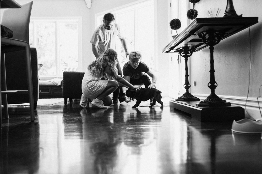 artistic-black-and-white-photo-of-family-playing-with-pug-dog-saltlakecity-utah