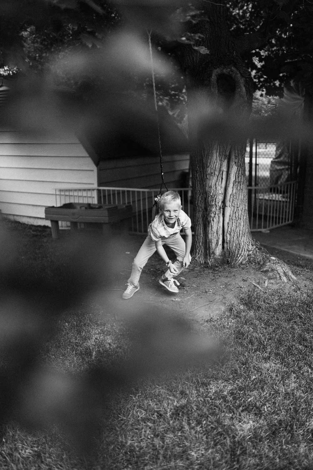 black-and-white-artistic-photo-of-boy-playing-on-swing-during-in-home-session-with-jen-fairchild-photography-slc-ut