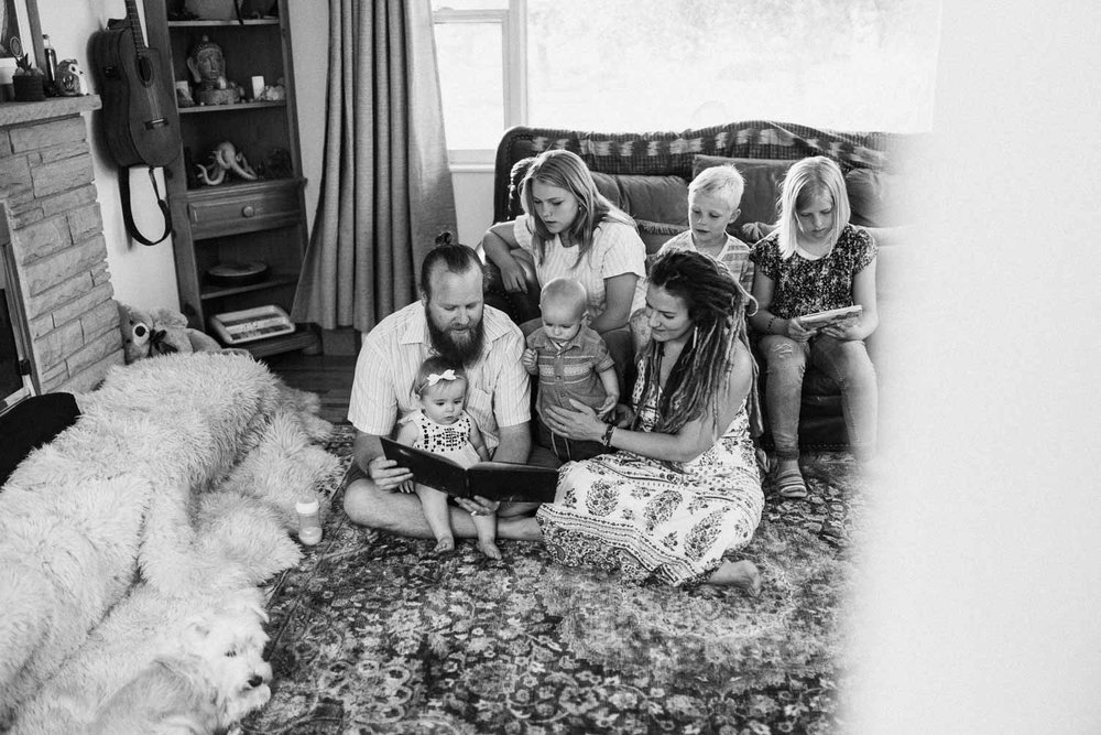 candid-black-and-white-family-photo-during-story-time-in-home-session-with-jen-fairchild-in-salt-lake-city-utah