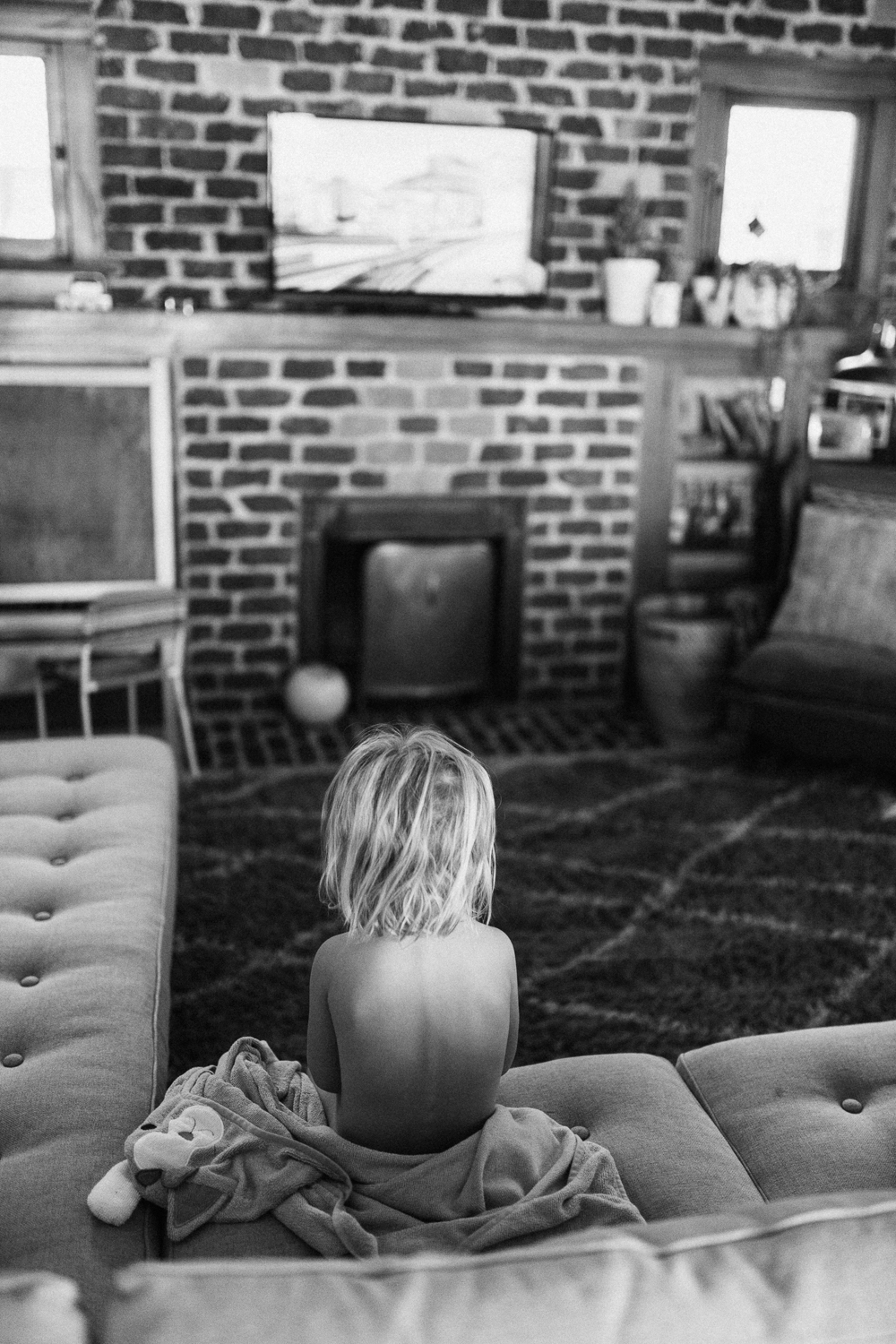 black-and-white-candid-photo-of-little-girl-sitting-on-couch-during-in-home-session-with-jen-fairchild-photography-slc-ut