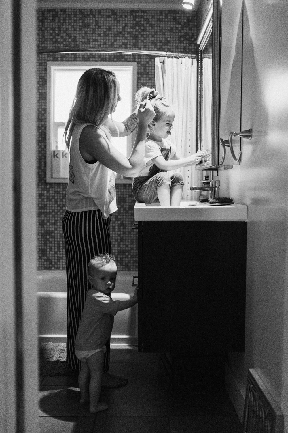 candid-black-and-white-photo-mom-doing-daughters-hair-in-bathroom-during-in-home-session-with-jen-fairchild-in-salt-lake-city-utah