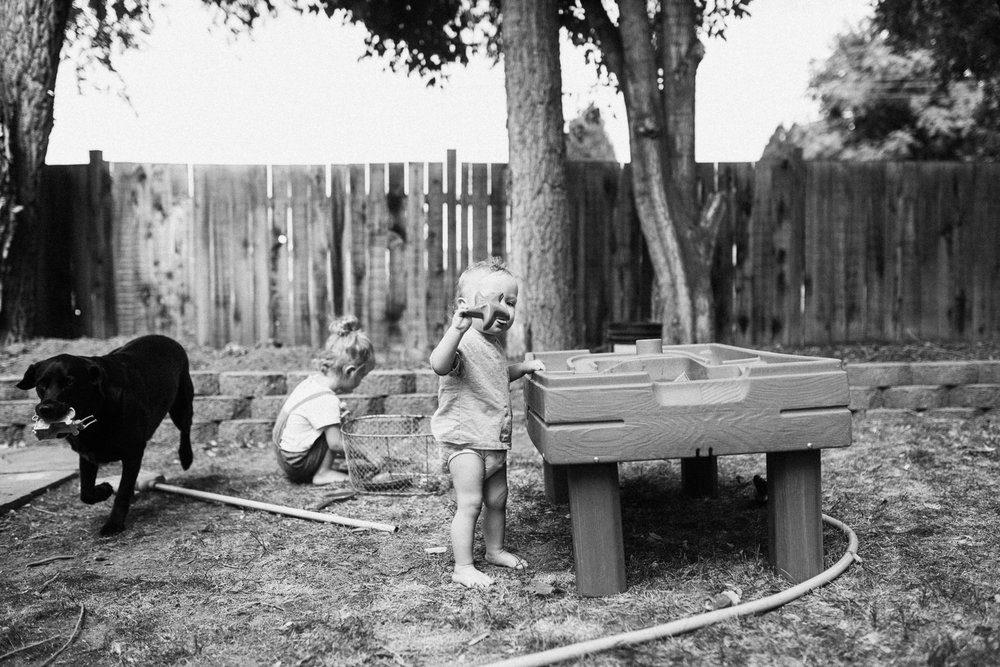 candid-black-and-white-photo-of-children-playing-in-backyard-with-dog-jen-fairchild-photography-salt-lake-city-utah