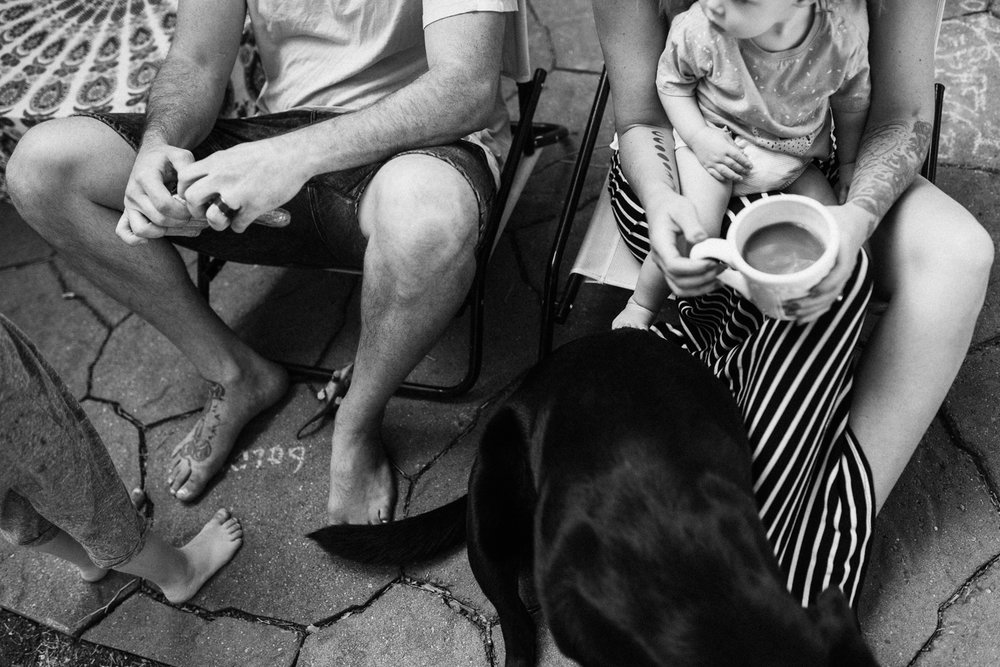 black-and-white-photo-of-family-sitting-on-chairs-outdoors-with-dog-salt-lake-city-utah