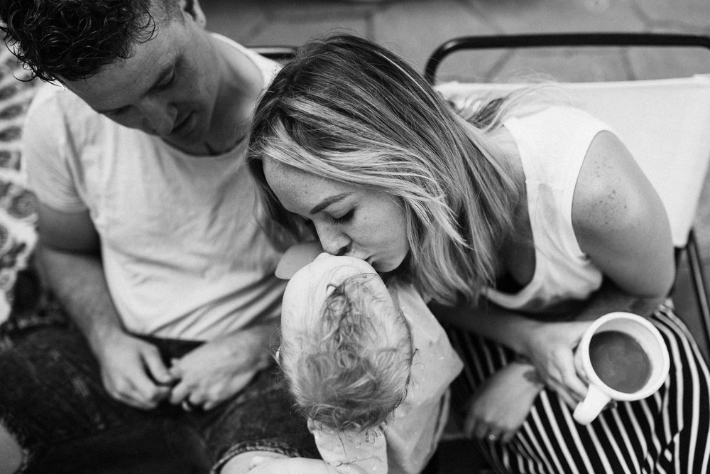 candid-black-and-white-photo-of-parents-kissing-child-slc-ut