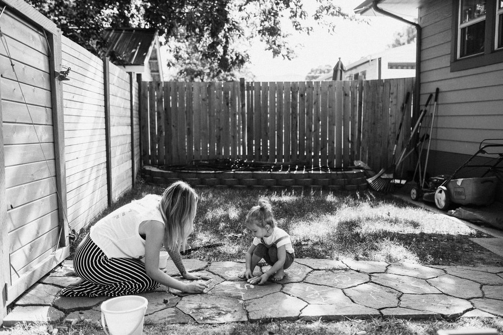 black-and-white-photo-of-mother-and-daughter-drawing-with-chalk-slc-utah